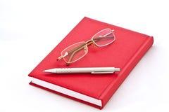 Gläser und die Feder auf dem Buch Stockfotografie