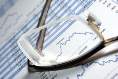 Gläser und Finanzreport mit Diagrammen. Stockbild