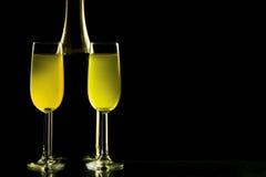 Gläser und Flasche Champagner lokalisiert auf einem schwarzen Hintergrund Lizenzfreies Stockfoto
