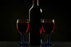 Gläser und Flasche Wein lokalisiert auf einem schwarzen Hintergrund Stockbilder