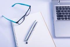 Gläser und leeres Notizbuch und Laptop im Büro Stockfotografie