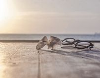 Gläser und Lotosblume, die auf einem Holztisch liegt Stockbild