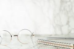 Gläser und Notizbuch auf Luxusmarmor lizenzfreies stockfoto