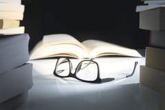 Gläser und offenes Buch auf der Tabelle umgeben durch Literatur stockfotografie