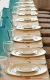 Gläser und Platten in einer Reihe Lizenzfreie Stockfotos