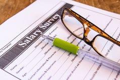 Gläser und Stift auf Gehaltsübersicht von Lizenzfreies Stockfoto