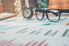 Gläser und Uhr auf dem Geschäftspapier Berichten Sie über Diagramm Stockfotografie