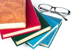 Gläser und verschiedene farbige Bücher Stockbild