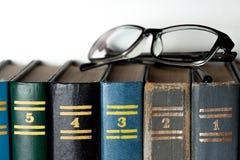 Gläser und verschiedene farbige Bücher Stockfoto