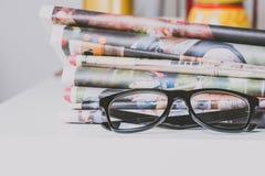Gläser und Zeitungen, Nahaufnahme Stockbild