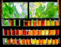 Gläser verschiedene Stärke Ahornsirupe, die in einem Fenster an einem Ahornsirup gesehen werden, bewirtschaften stockbilder