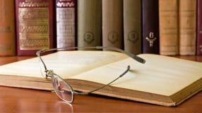 Gläser vor alte Bücher Stockfotos