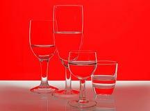 Gläser vor einem roten und weißen Hintergrund stockfotos