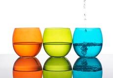 Gläser Wasser, Gelbgrün, Orange, Türkisfarben weiß Stockbild