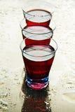 Gläser Wein auf einem nassen Spiegel. Stockfotos