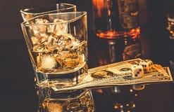 Gläser Whisky nahe Flasche auf Dollar Geld und Spiel würfeln auf einer schwarzen Tabelle Stockfoto