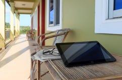 Gläser, Zeitung und Laptop auf Holztisch im Motelbalkon Stockfotos