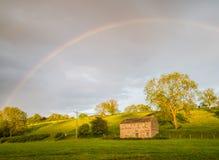 Glättende Yorshire-Täler, Landscheune und Regenbogen Stockfotografie