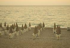 Glättung des leeren Strandes mit Stühlen und gestreiften Regenschirmen Erholungsortlandschaft Retro- Filter der Weinlese stockfoto