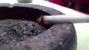 Glöd av en cigarett över ett askfat royaltyfri bild