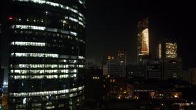 Glödande fönster av skyskrapor på aftonen - sikt av moderna torn i staden av Abu Dhabi stock video