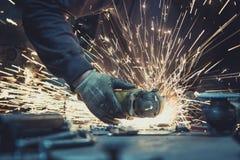 Glödande flöde av gnistor gjorde, genom att såga ett stycke av stål med en vinkelmolar på en arbetsyttersida Fotografering för Bildbyråer
