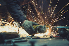 Glödande flöde av gnistor runt om en vinkelmolar, medan klippa ett stycke av stålrörröret på en arbetsyttersida Fotografering för Bildbyråer