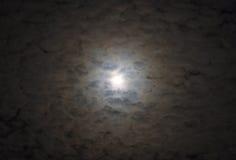 Glödande fullmåne som omges av lager av tända lynniga mjuka moln arkivbilder