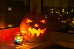 Glödande halloween pumpa och kopp Fotografering för Bildbyråer