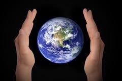 Glödande jordjordklot i händer på svart, miljöbegrepp - beståndsdelar av detta bild som möbleras av NASA royaltyfri fotografi