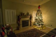 Glödande julträd med ljus som glöder i en annars mörk vardagsrum arkivfoton