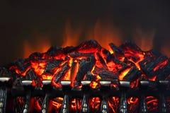 Glödande kol och brandflammor i spis royaltyfri bild
