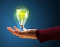 Glödande lightbulb i handen av en kvinna Arkivbilder