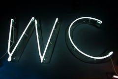 Glödande neonWC undertecknar för offentligt toaletttecken Skinande bokstäver som visar vägen för toalett Royaltyfri Foto