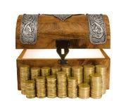 Glödande skattbröstkorg och kolonner av guld- mynt Arkivfoto
