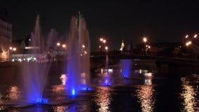 Glödande springbrunnar i floden och lyktor på brobakgrund i Moskva på natten stock video