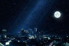 Glödande stad med den ljusa månen och många stjärnor i himmel Royaltyfri Bild