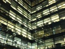 Glödande upplysta fönster i en stor modern geometrisk stadskontorsbyggnad på natten som visar arbetsutrymmen arkivfoton