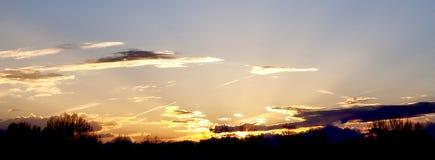 Glödande vintersolnedgång med moln arkivbild