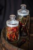 Glödheta chilipeppar i en glass krus Fotografering för Bildbyråer
