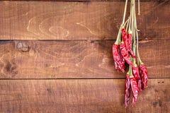 Glödheta chilipeppar på en träbakgrund arkivfoto