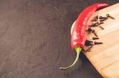Glödheta peppar och kryddor på en tom skärbräda/glödheta chilipeppar och kryddor för chili på en tom skärbräda på ett mörker arkivbild