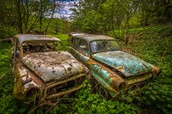 Glömd bil som förfaller i trädgården fotografering för bildbyråer