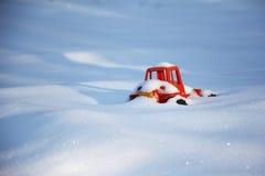 Glömda barns leksak i snön som är dold med snö Arkivbilder