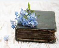 Glömma-mig-nots blommor och gammal bok Royaltyfri Fotografi