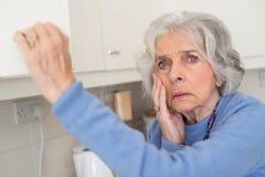 Glömsk hög kvinna med demens som ser i skåp arkivbild