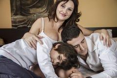 Glück, Familie mit der schwangeren Mutter, die sich zusammen auf Bett entspannt stockfoto
