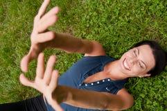Glück - Frau, die im Gras liegt Stockfotografie