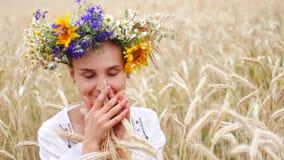 Glück, Natur, Sommerferien, Ferien und Leutekonzept - lächelnde junge Frau im Kranz von Blumen entlang gehend stock video footage
