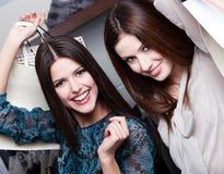 Glück von zwei Freundinnen nach dem Einkauf Stockbilder